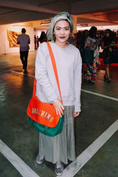 Potti Lesaguis matches her outfit with her silver hair, and adds a pop of color with a statement Moschino messenger bag.